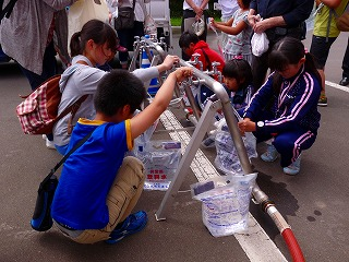 Photograph of children pouring water into water supply bag