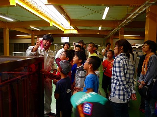 Photograph 1 of children receiving explanation at fishing river water purification plant